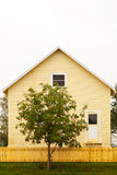Yellow House and Fence with Red and Green Tree Royalty Free Stock Photography