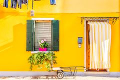 Yellow house with flowers and plants. Colorful houses in Burano island near Venice, Italy. Stock Photo