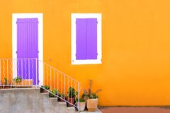 Yellow house front with purple shuttered door and window Royalty Free Stock Image