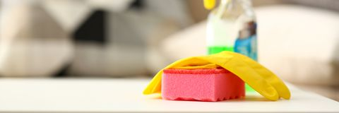 Yellow house glove lying on pink sponge as symbol of chore routine work. Letterbox view of yellow house glove lying on pink sponge as symbol of chore routine royalty free stock images