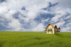 Yellow house on grass field. With nice sky stock image