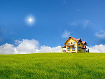 Yellow house on grass field. With nice sky stock photos