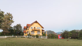 Yellow house with grass field Stock Images