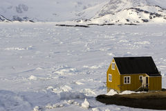 The yellow house on the ice floe. Wood house on frozen sea coast of Kulusuk, Greenland Stock Photos