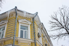 Yellow house with icicles hanging from the roof Royalty Free Stock Photos