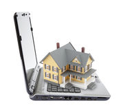 Yellow house on laptop Stock Photography