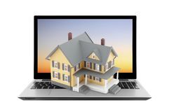 Yellow house on laptop Stock Photos