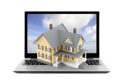 Yellow house on laptop Stock Photo