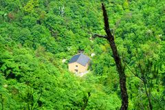 A yellow house in a mountain filled with green trees Stock Image