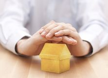 Yellow house protected by hands Stock Image