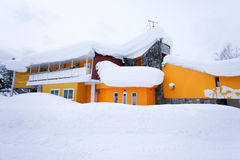 Yellow house in snow Royalty Free Stock Image