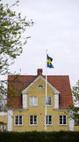 Yellow house with swedish flag. Royalty Free Stock Photo