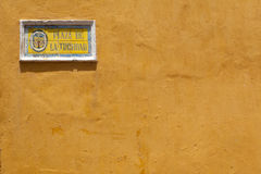 Yellow house wall with tiled street sign Stock Photos