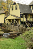 Yellow house with a waterwheel and waterfall Royalty Free Stock Photo