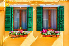 Yellow house and window with green shutters Royalty Free Stock Photo