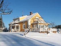 Yellow House in Winter. Yellow wooden traditional home in Finland covered in snow on a sunny winters day with blue sky Stock Photo