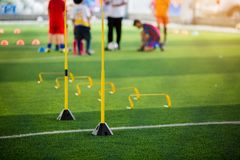 Yellow hurdles and ladder drills on green artificial turf. With blurry coach and kid soccer are training royalty free stock images