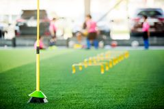 Yellow hurdles and ladder drills on green artificial turf with blurry coach and kid soccer. Are training royalty free stock photo