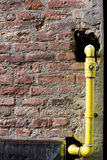 Yellow hydraulic hose coming out of a brown brick wall. Royalty Free Stock Image