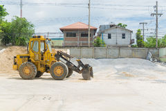 Yellow hydraulic tractor loader or Backhoe earthmover woking in. Construction site for stone and sand grading Stock Photo