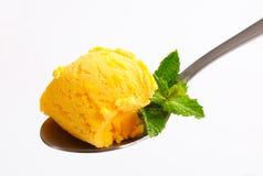 Yellow ice cream on spoon Stock Images