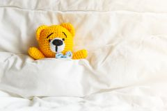 Yellow ill teddy bear lying in bed on white background. Royalty Free Stock Photos