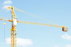 Yellow Industrial crane and blue sky on construction site Stock Images