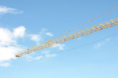 Yellow Industrial crane and blue sky on construction site or seaport Royalty Free Stock Photos