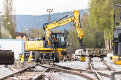 Yellow industrial excavator near railway Royalty Free Stock Photo