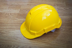 Yellow industrial protective helmet on wooden background Royalty Free Stock Photo