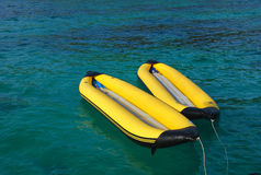 Yellow inflatable boats floating in the sea. Two yellow inflatable boats floating in the sea Stock Images
