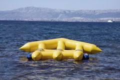 Yellow inflatable in ocean. Large yellow inflatable object used for sport floating in blue ocean Royalty Free Stock Images