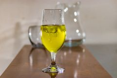 Yellow liquid on table in glass. Yellow ink swirling in water with other empty glasses behind on table royalty free stock photography