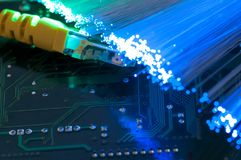 Yellow internet switch close up macro shot on computer circuit board. Glowing optical fibres Royalty Free Stock Image
