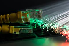 Yellow internet switch, glowing optical fibres on laptop computer. Close up macro shot stock photography