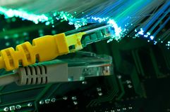 Yellow internet switch , grey switch close up macro. Shot on computer circuit board, glowing optical fibres Stock Photos