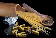 Yellow Italian pasta, spaghetti, black pepper against the black isolated background. A beautiful still life. A close-up stock photos