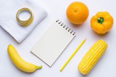 Yellow items. Fitness concept with banana, coin, orange, measuring tape on white background. View from above Royalty Free Stock Photography