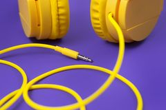 Yellow jack plug cable and headphones on purple background. Music concept. Yellow jack plug cable and headphones on purple background. Music concept Royalty Free Stock Photo