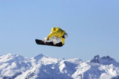 Yellow Jacket Snowboard air. A snowboarder in bright clothes does an extreme air high in the mountains on a blue sky day Royalty Free Stock Images