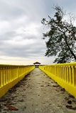 Yellow Jetty With Two Friend Sitting at The End Royalty Free Stock Photos