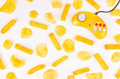 Yellow joystick and potato chips. Harmful food and gamepad. GamePad. Yellow joystick and potato chips. Harmful food and gamepad. Copy space Royalty Free Stock Photography