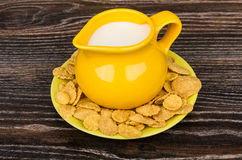 Yellow jug milk in saucer with corn flakes on table Royalty Free Stock Image