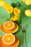 Yellow jug with yellow tulips and juicy oranges Royalty Free Stock Photos
