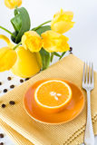 Yellow jug with yellow tulips and juicy oranges Royalty Free Stock Image