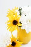 Yellow jug with yellow and white flowers on a background Stock Photos