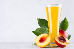 Yellow juice in glass and juicy ripe red nectarines with green leaves, slice, seed on soft light white wood board, closeup. Healthy dieting food royalty free stock photo