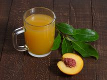 Yellow juice in glass mug and peach with leaves on the table. Royalty Free Stock Photos
