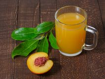 Yellow juice in glass mug and peach with leaves on the table. Royalty Free Stock Image