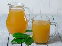 Yellow juice in glass pitcher and mug on the table. Stock Photos